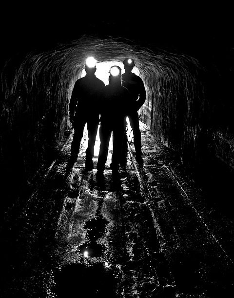 three miners in a gold mine tunnel